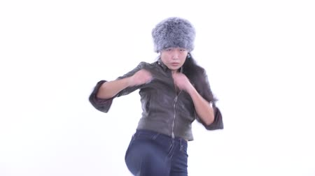 Beautiful Asian woman doing martial arts and ready for winter