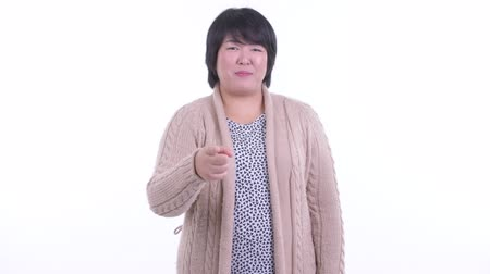 Happy overweight Asian woman pointing at camera ready for winter