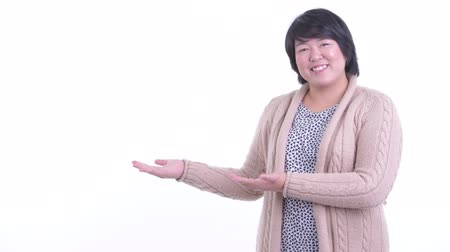 Happy overweight Asian woman showing something for winter