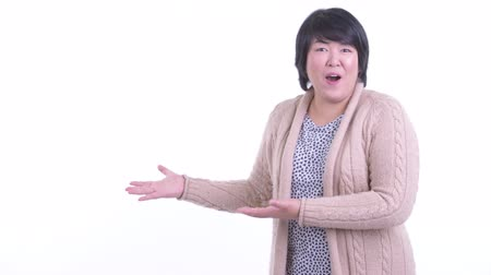 Surprised overweight Asian woman showing something for winter