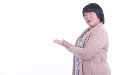Happy overweight Asian woman talking while showing to the back for winter