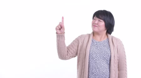 Happy overweight Asian woman pointing up ready for winter Dostupné videozáznamy