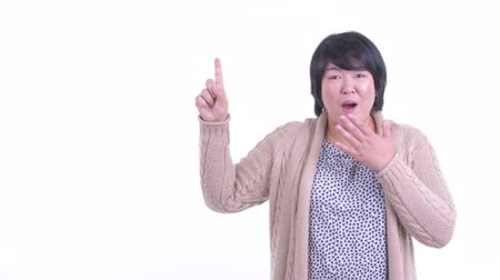 Surprised overweight Asian woman pointing up ready for winter