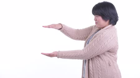 Happy overweight Asian woman snapping fingers and showing something for winter Dostupné videozáznamy