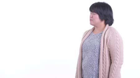 Happy overweight Asian woman touching something and ready for winter