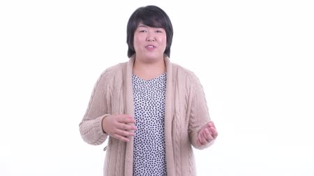 Happy overweight Asian woman talking to camera and ready for winter Dostupné videozáznamy