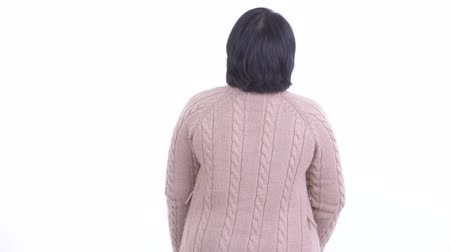 kısa : Rear view of happy overweight Asian woman thinking and looking around in winter Stok Video