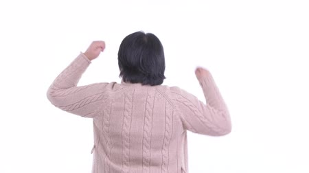 emelt : Rear view of happy overweight Asian woman with fists raised ready for winter