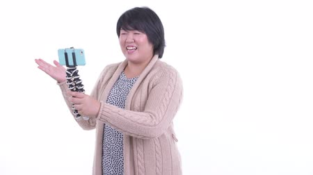 tripod shot : Happy overweight Asian woman vlogging with phone ready for winter