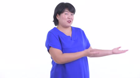 nadváha : Happy overweight Asian businesswoman presenting something