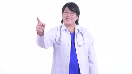 direkt : Happy overweight Asian woman doctor pointing finger and directing Stok Video