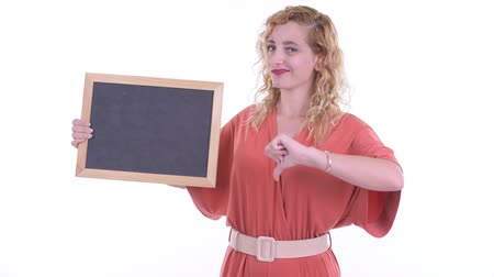 разочарование : Stressed blonde businesswoman holding blackboard and giving thumbs down Стоковые видеозаписи