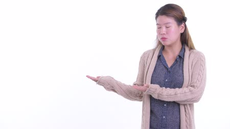 gestos : Stressed young Asian woman showing something and getting bad news for winter