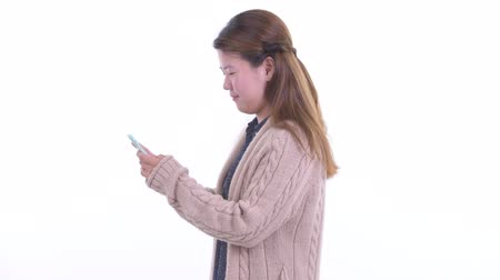 taken : Profile view of young Asian woman with phone being taken away for winter