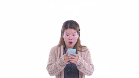 в середине : Happy young Asian woman using phone and looking surprised ready for winter