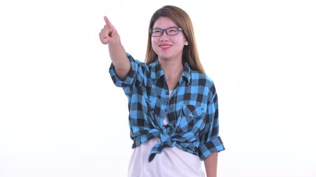 přímý : Happy young Asian hipster woman pointing finger and directing