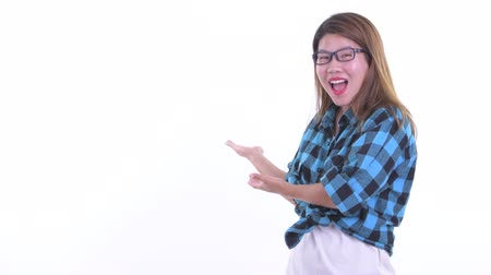 Excited young Asian hipster woman showing to the back Dostupné videozáznamy