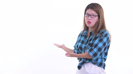 Stressed young Asian hipster woman showing to the back