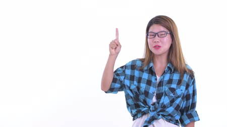 Happy young Asian hipster woman talking while pointing up