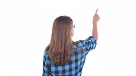 Rear view of young Asian hipster woman pointing finger and directing