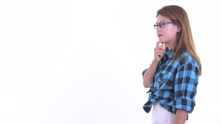 Profile view of happy young Asian hipster woman thinking