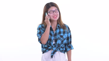 Happy young Asian hipster woman talking on the phone
