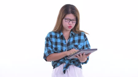 Happy young Asian hipster woman talking while using digital tablet