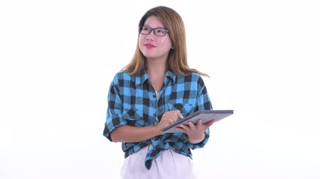Happy young Asian hipster woman thinking while using digital tablet