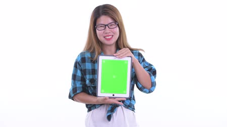 Happy young Asian hipster woman talking while showing digital tablet Dostupné videozáznamy