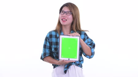 Happy young Asian hipster woman thinking while showing digital tablet