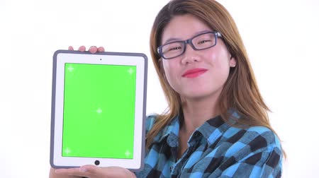 Face of happy young Asian hipster woman showing digital tablet