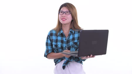 Happy young Asian hipster woman thinking while using laptop