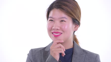 Face of happy young beautiful Asian businesswoman thinking and looking up