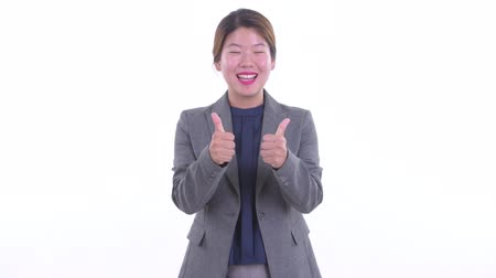 Happy young Asian businesswoman giving thumbs up and looking excited