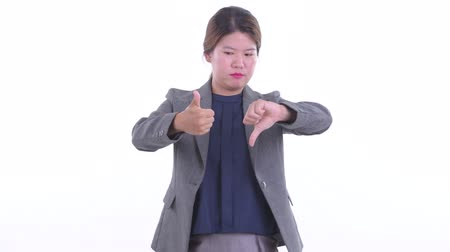 Confused young Asian businesswoman choosing between thumbs up and thumbs down
