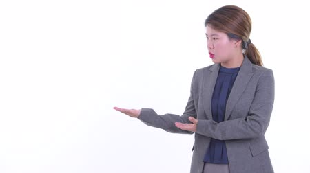 Stressed young Asian businesswoman talking while showing something