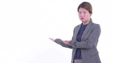 Stressed young Asian businesswoman talking while showing to the back