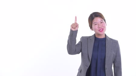 Happy young Asian businesswoman talking while pointing up