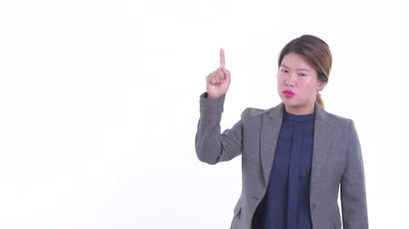 Stressed young Asian businesswoman talking while pointing up Dostupné videozáznamy