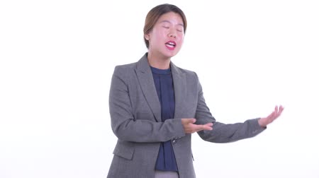 Happy young Asian businesswoman presenting something Dostupné videozáznamy
