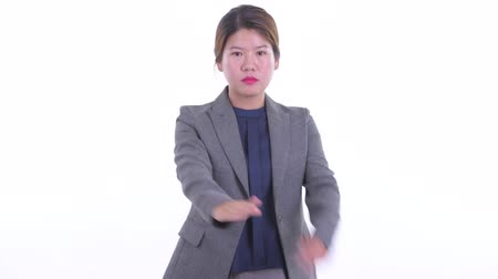 Serious young Asian businesswoman with stop gesture
