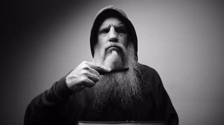 különc : Mature bald bearded man in hoodie combing beard with dramatic shot