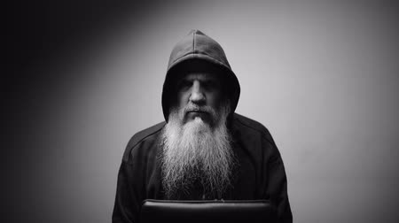 különc : Mature bald bearded man in hoodie looking at camera with dramatic shot