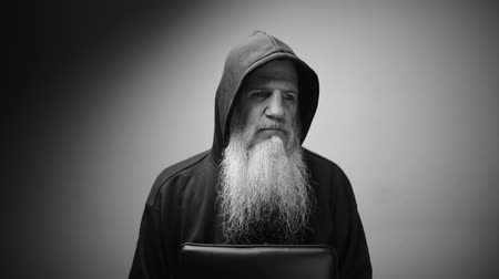 különc : Mature bald bearded man in hoodie thinking with dramatic shot