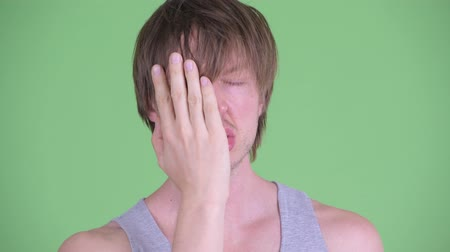в середине : Face of stressed young man with messy hair showing face palm gesture Стоковые видеозаписи
