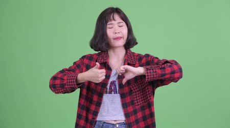 fikirler : Confused Asian hipster woman choosing between thumbs up and thumbs down Stok Video