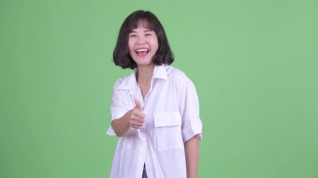 Happy beautiful Asian businesswoman giving thumbs up Dostupné videozáznamy