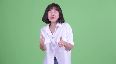 Happy beautiful Asian businesswoman giving thumbs up and looking excited