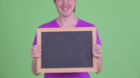 в середине : Happy young handsome man holding blackboard Стоковые видеозаписи