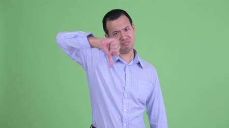pouce vers le bas : Studio shot of angry Asian businessman giving thumbs down Vidéos Libres De Droits